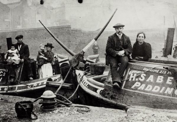 "Caption: ""Black and white photograph showing boat people on the H Sabey & Co Paddington wide boats. The boats are stern to stern on the canal. People shown include Tom 'Cheshire' (real name Garner), Caroline Kendall nee Garner (mother of A Kendall), A Kendall in his mother's arms, Harry and Lizzie Bland (uncle and aunt of A Kendall)."""