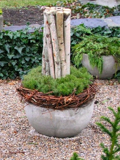 "I like this ""sculpture"". I love the idea of using a wreath on top of the container. I think I may leave the branches a bit longer...depending on the container used."