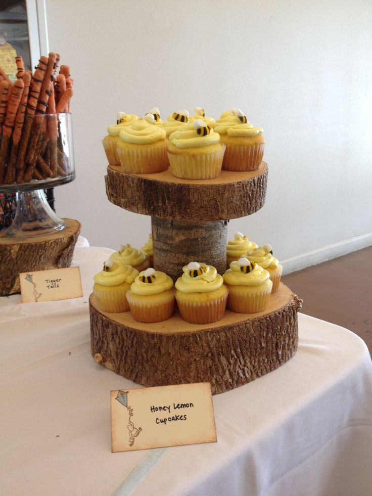 Lemon cupcakes for classic Winnie the Pooh baby shower on wood cupcake stand