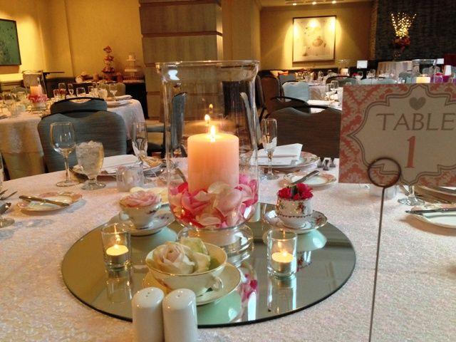 A Vintage Wedding Centerpiece With China Teacups And Saucer Filled Pink Roses Surrounds Hurricane Pillar Candle Rose Petals