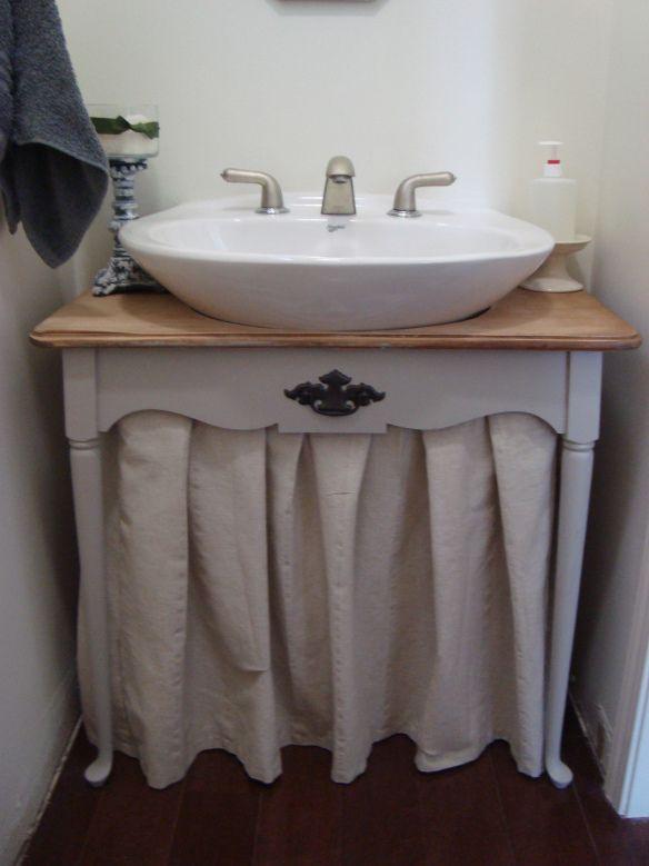 One way to hide a hideous builder cheap pedestal sink, throw a skirt on it.