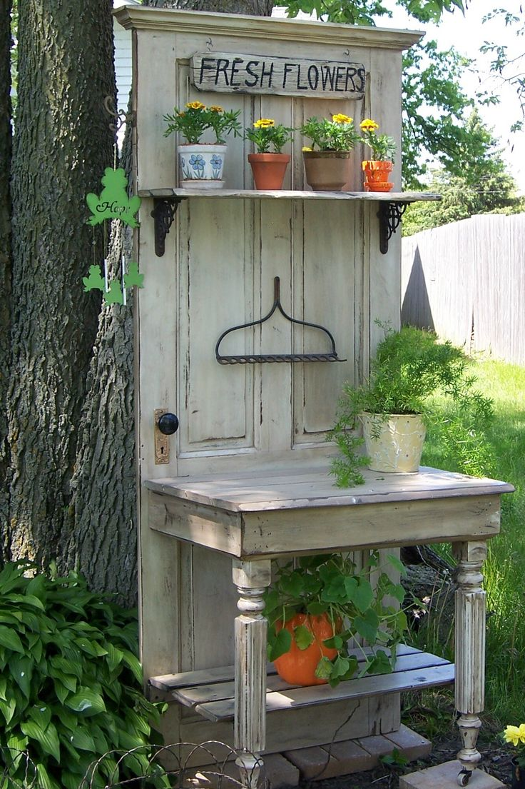 My husband  a friend constructed this from an old door, half a table and the metal part of a rack.  It makes a nice accent in the corner of our yard between two flower beds.