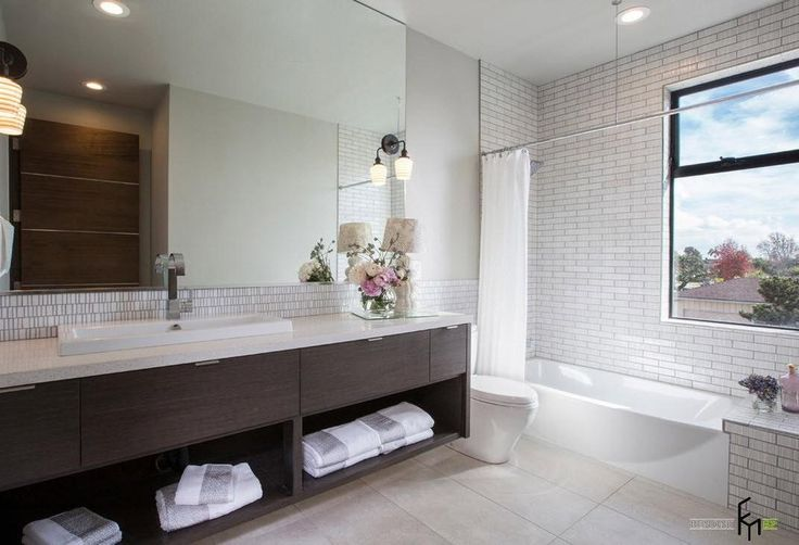 An inspiring bathroom with white tile wall and shiny bathtub with stylish brown storage and large frameless mirror and lovely flower decors