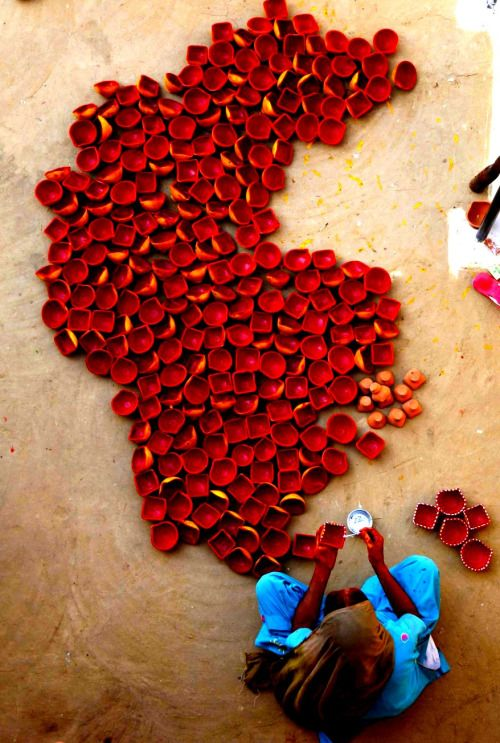 my-spirits-aroma:  An Indian woman paints earthen lamps on the outskirts of Jammu ahead of Hindu festival Diwali. Diwali, the festival of lights!!
