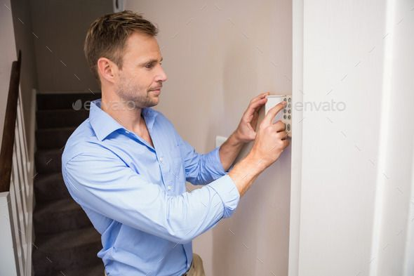 Man arming a home alarm on the wall. http://photodune.net/item/man-arming-a-home-alarm-on-the-wall/9621670