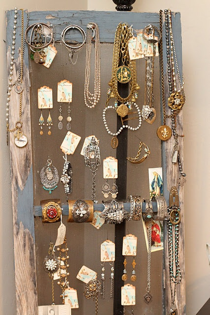 great vertical jewelry display: framed screen, with hooks holding earring cards, necklaces hanging off sides...