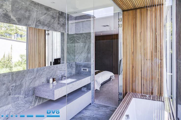 Modern Japanese bathroom. Interplay of solid stone and tectonic timber elements. Timber screening is repeated on ceiling. Wabi Sabi.