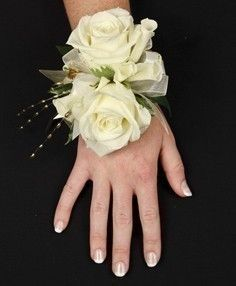 Corsage with double white roses and white ribbon.