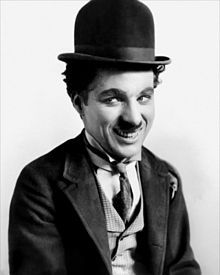 A smiling man with a small moustache wearing a bowler hat and a tight-fitting necktie and coat