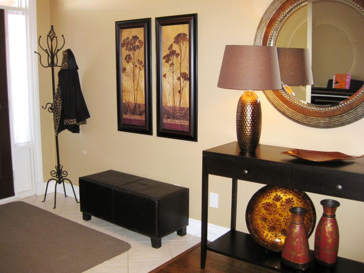 Earth tones set the mood in this entrance. A practical bench for pulling on boots, while the table supports a much needed lamp and a mirror for last minute touch-ups.