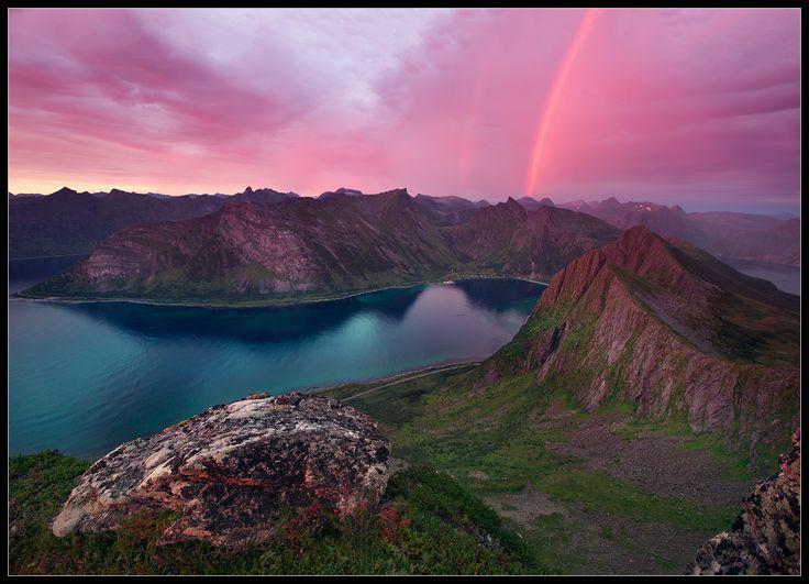 Горное озеро, разделенное на две части горной грядой, на фоне розовых облаков и ярко светящейся радуги
