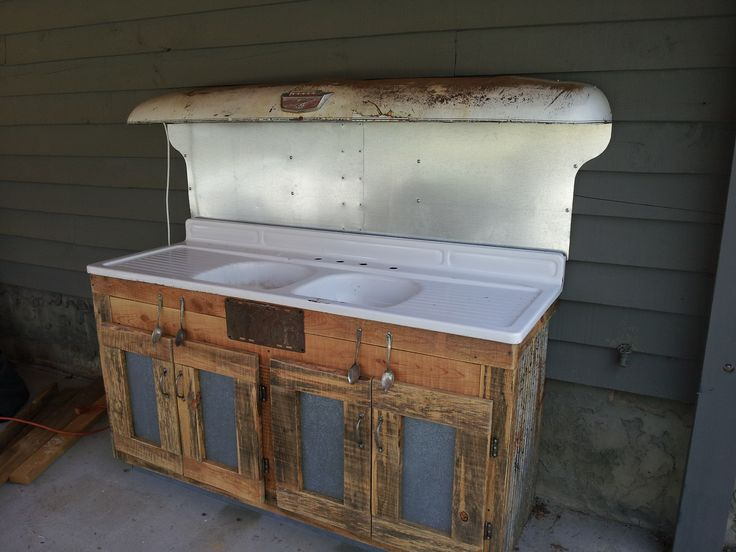 An enameled steel double sideboard sink, rough-cut sawmill lumber, galvanized sheet metal, and a hood from an old Ford pick-up...... the start of our outdoor kitchen.