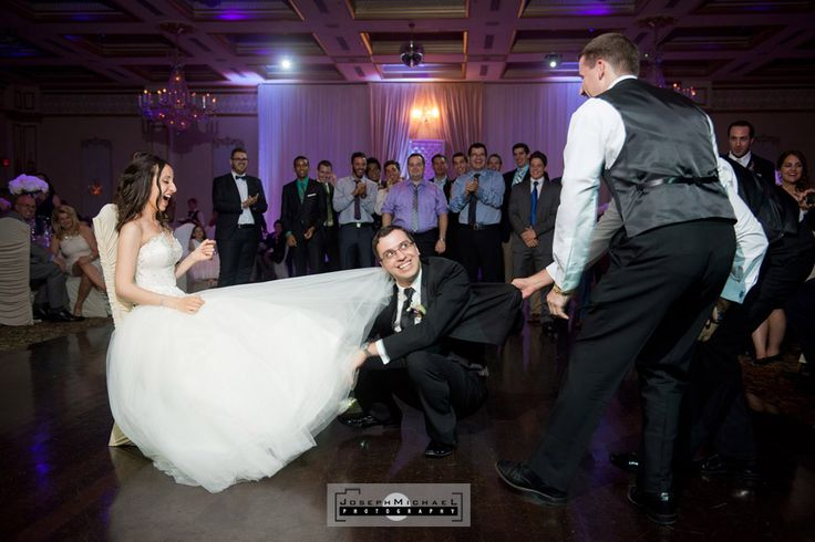 Venetian Banquet Hall Wedding Photography Toronto, Groom going for garter and getting pulled out, funny wedding photos.