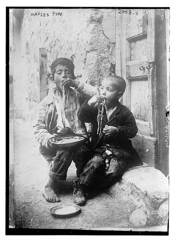 vintage photo two boys eating pasta on streets of Naples 1900
