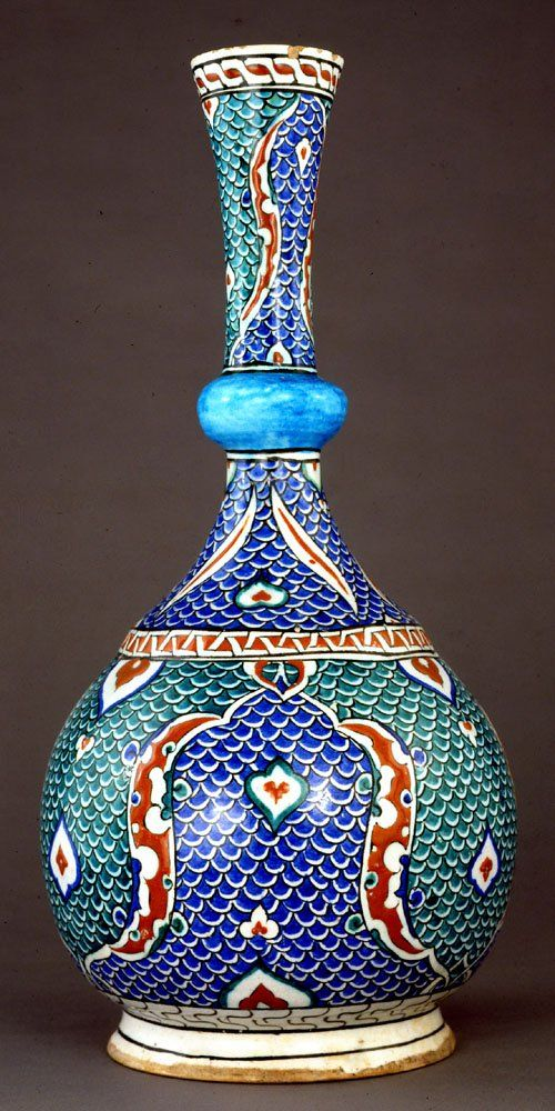 Flask. Horizontal tiers of scale panels,bordered by attenuated sausages.Drawn from Venetian glass,scale pattern from Bursa textiles. Made of red (bole) painted and glazed ceramic, pottery.