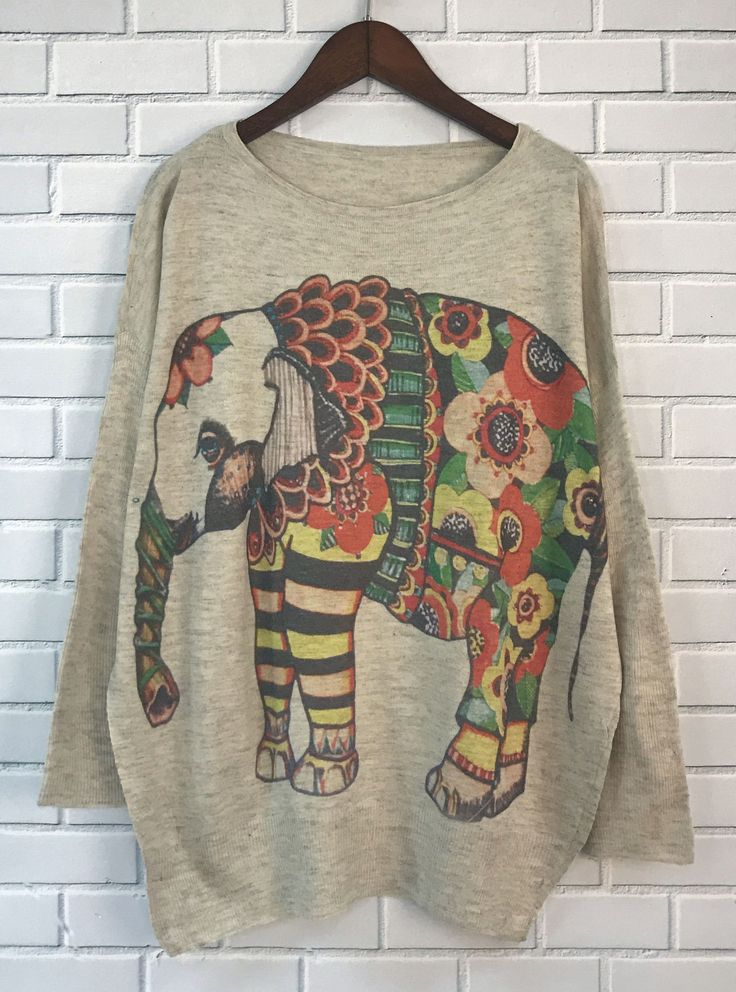 A knit sweater featuring elephant graphic with floral print, batwing sleeve, a round neckline and ribbed trim.