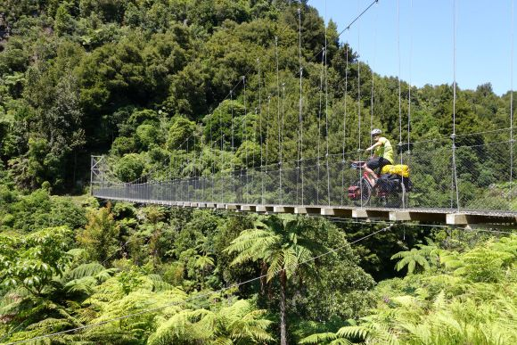 Riding across Mangatukutuku Bridge (part of the Timber Trail – an 85 km cycle trail that passes through Pureora Forest Park and is part of Nga Haerenga, The New Zealand Cycle Trail).
