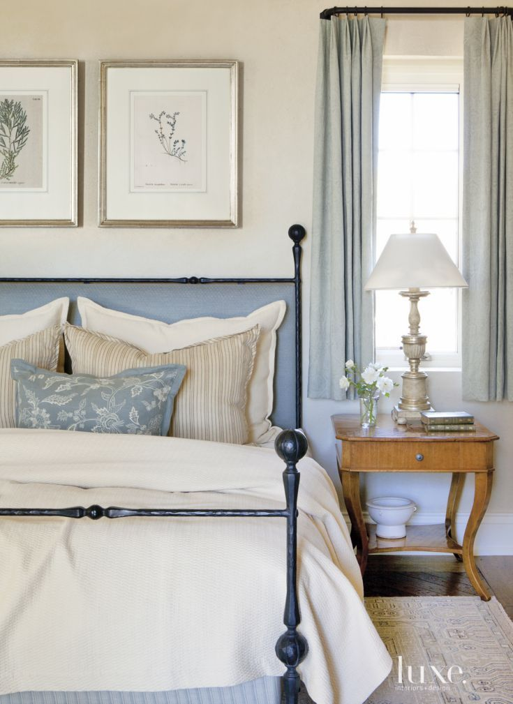 Mediterranean White Bedroom with Blue Hues Soft blues and creamy neutral hues set a soothing tone in the master bedroom, where a Dessin Fournir bed, with a headboard upholstered in blue Rogers & Goffigon fabric, resides next to an AK Josephine side table from the Kerr collection in Dallas. The Ravenna candlestick lamp is by Minton-Spidell.