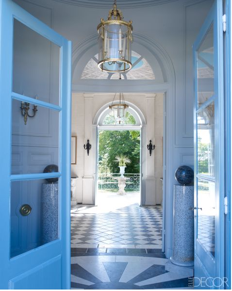 Bright blue entryway doors and a beautiful faux candlelight brass fixture