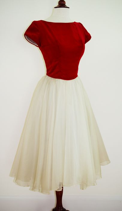 This is a 1950s Emma Domb party dress with a red velvet fitted bodice and iridescent pearl sheer organza skirt which floats over a taffeta underskirt.