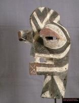 Masque Kifwebe masculin décoré de fines rayures brunes et blanches. Comme de coutume chez les masques kifwebe masculins une crête part du nez et s'élève sur le sommet de la tête. Ce masque qui fait partie des masques africains les plus originaux ils sont utilisés pour les circoncisions, initiations et funérailles. Les masques masculins s'agitent de façon désordonnée et brutale. Ce faisant ils font l'apologie des règles de vie en société.