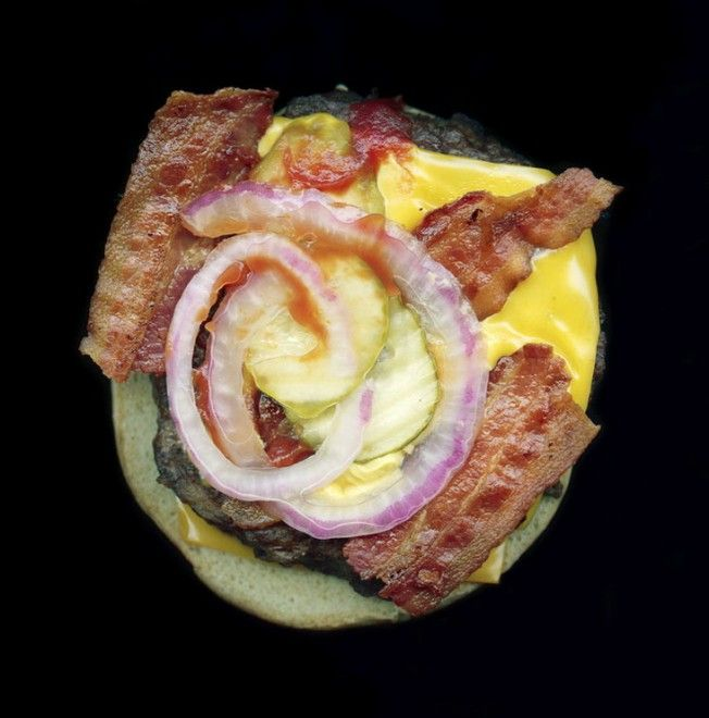 """Hamburger, patatine fritte, pepite di pollo e panini del fast food sono i protagonisti del progetto fotografico di  Jon Feinstein . Tanto amato in tutto il mondo dagli anni '50, il """"cibo veloce"""" viene illustrato su sfondo nero, spogliato da ogni tipo di marchio e iconografia che lo rende a"""