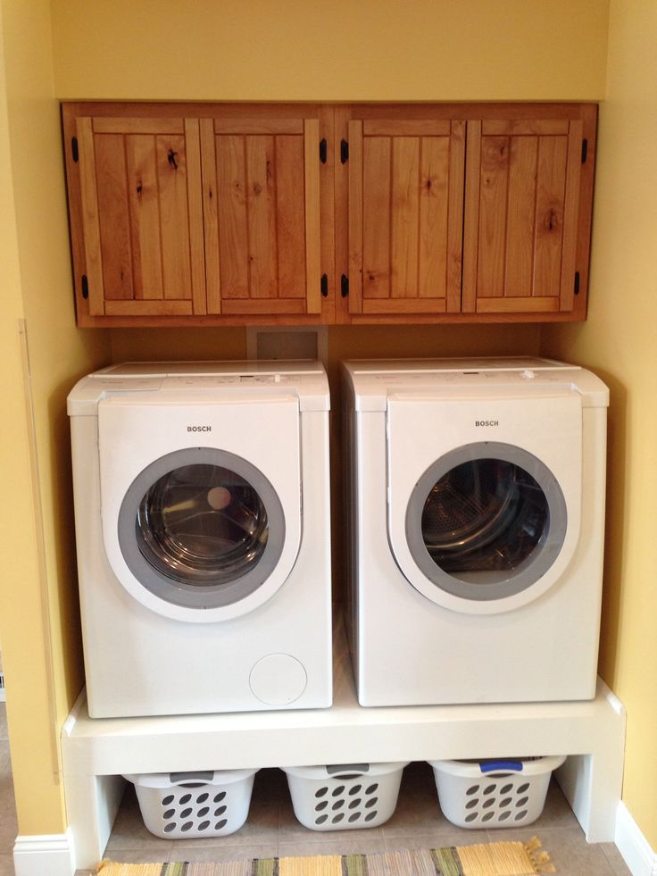 Love my cabinets and storage for clothes baskets under the washer/dryer