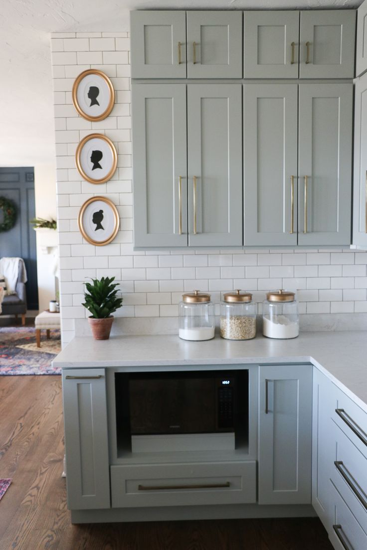 Beautiful pale green gray neutral cabinets with brushed gold hardware and subway tile to the ceiling