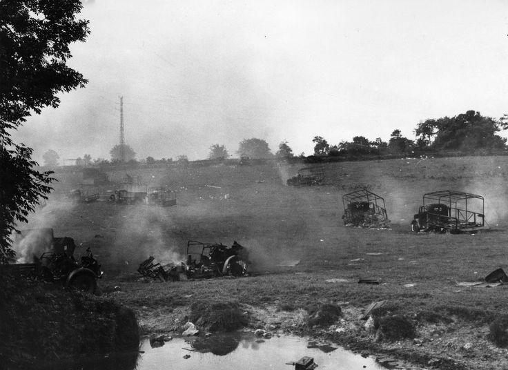Embarquement des troupes britanniques à Cherbourg en juin 1940,  Véhicules incendiés dans une prairie près de la RN13 en arrière plan un pylône métallique d'une ligne électrique HT.