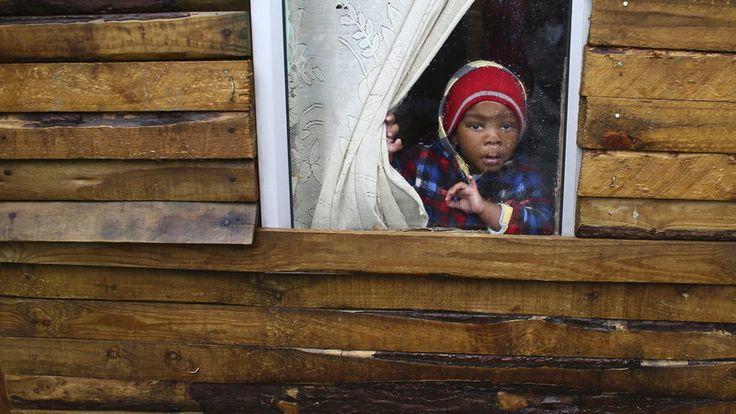 15. August, #Südafrika: Nach heftigen Regenfällen sind Teile von Armensiedlungen in Cape Town überschwemmt. Tausende Menschen mussten in Notunterkünften untergebracht werden. Dieses Kind schaut aus dem Fenster einer von der Überflutung betroffenen Bretterhütte. Foto: dpa  Weitere Bilder unter: www.noz.de/74078614