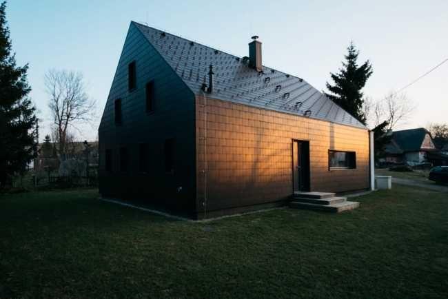 Skládaná vláknocementová krytina antracitové barvy je použita na střeše i fasádě a svým drobným měřítkem odkazuje na doškové střechy.