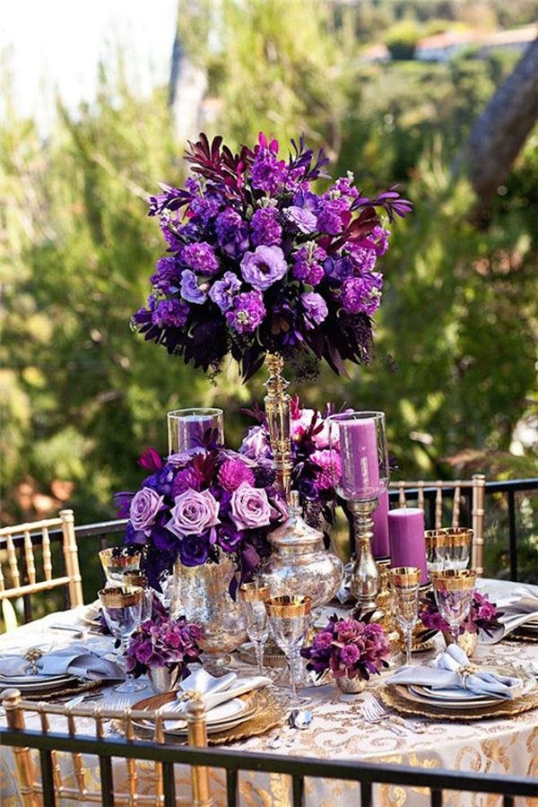 Dark purple tall wedding centerpiece ideas for winter weddings. Accented with gold leaf charger plates, gold cutlery and gold rimmed glasses. #purplewedding