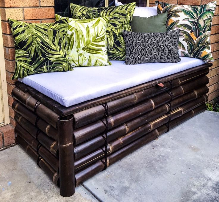 Bamboo garden bench seat ( made from an off-the-shelf fencing panel and given an extra coat of black japan stain ) with built in storage and tropical foliage print cushions