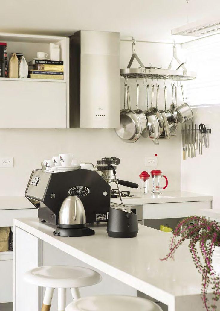 El ritual del café. Diseñada en tonos claros para mantener el estilo general de la vivienda y atraer la gran cantidad de luz natural que la inunda, esta cocina de pequeño tamaño refleja inmediatamente los intereses de los propietarios: él, especialista en café y ella, en panadería.