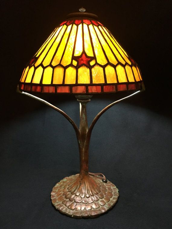 """""""Star Geometric"""" (10"""") in gold and red art glass. Coughran Studios original design stained glass lamp, displayed on Three Legged Ruffle Base. """"Wildflowers of Texas"""" series. This diminutive gem appeals to men and women alike, and is especially at home in a Southwestern style decor."""