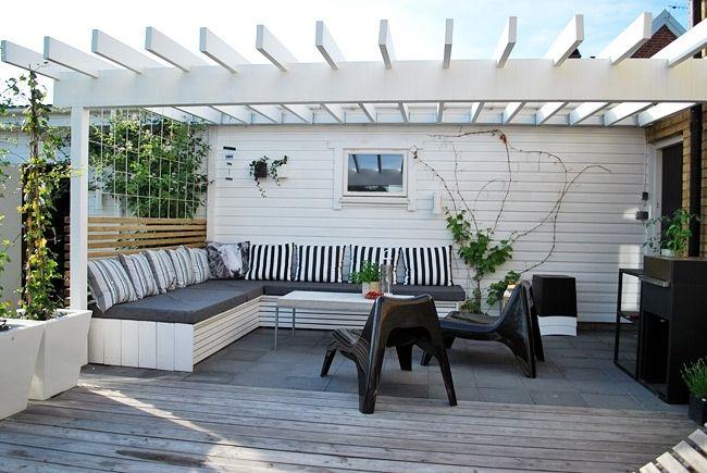 Vit pergola direkt utanför hus, platsbyggd bänk/soffa, spaljé som ryggstöd.