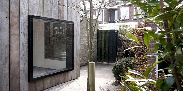 Frameless window in wooden facade. Garden studio