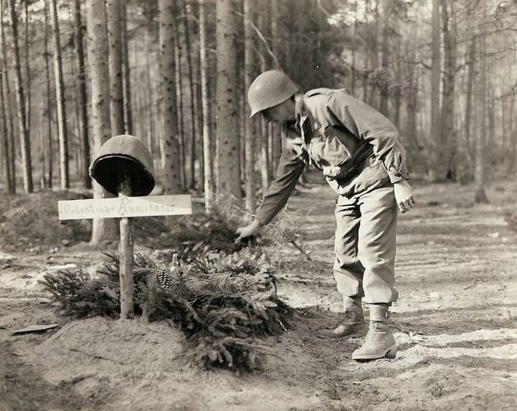 A U.S. soldier examines the grave of an unknown American soldier, who was buried by the enemy before retreating. The first American soldier that noticed the grave decorated it with mortar shells and ferns.