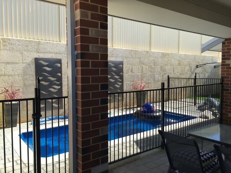 Backyard pool against retaining wall. View from our alfresco.