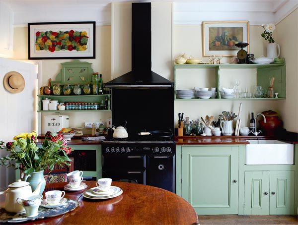 Pretty cottage kitchen in the UK, with green cabinets and shelves and black cook stove