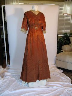Late 1900s/Early Teen Era Copper Dress. Stunningly beautiful shiny messaline silk copper color and fabric details highlight this lovely Edwardian dress. The un-boned bodice is covered in matching soutache braid. Ecru colored Irish lace adorns the neckline and three-quarter sleeves. A gold metal buckle trims the tiny waist. The skirt is pin-tucked at the waistline and falls fully to a slight train. Two matching fringed tassels hang from the waist down the back of the skirt. Hook and eye…