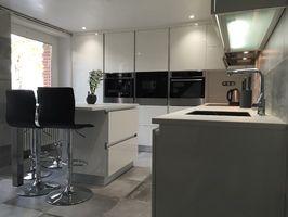 Cuisine blanche avec meubles haut jusqu'au plafond, hotte integré aux meubles et ilot servant de  plan de travail et table pour 4