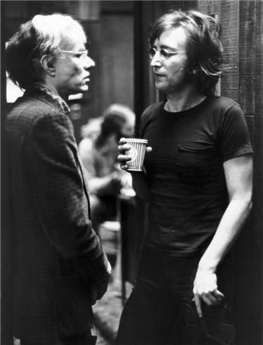 Andy Warhol and John Lennon | conversing in the corridor | talking | chat | meeting of the minds and creative arts | black & white photography | moment captured | coffee | discussion