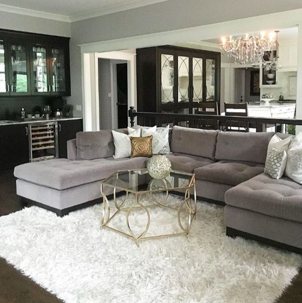 Gray sectional, black built ins and white shag rug