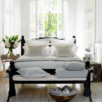 White summer bedroom with wooden floor and shutters