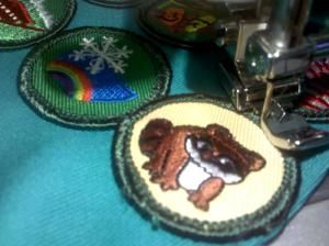 Learn how to sew on a girl scout badge by hand or machine, and the proper placement of patches on a Daisy, Junior and Brownie uniform.: Sewing on Girl Scout Badges by Machine