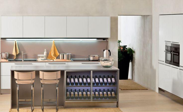 Temiz kaplı mobilya ve aletler bu mutfağın beyaz dolapları ile harika uyum yakalıyor. Şık beyaz dolaplar ile eşleştirilmiş ahşap sandalyelerve  bej rengine boyalı tavan yemek pişirmek ve