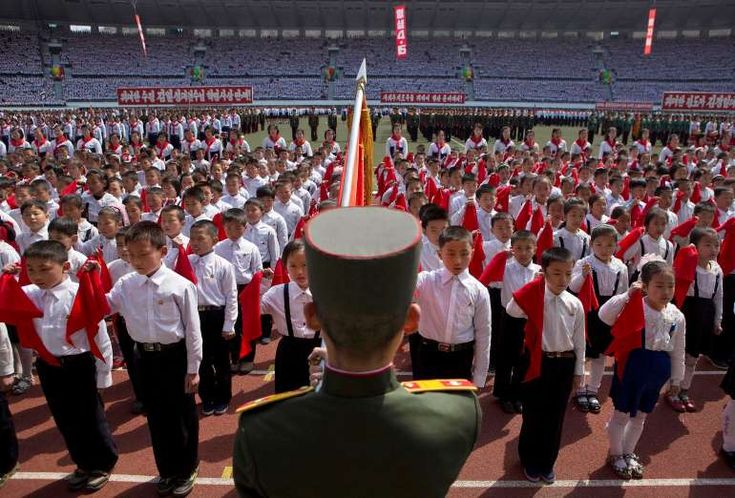North Korean children hold up red scarves to be tied around their necks during an induction ceremony into the Korean Children's Union, the first political organization for North Koreans, held at a stadium in Pyongyang on Friday, April 12, 2013.