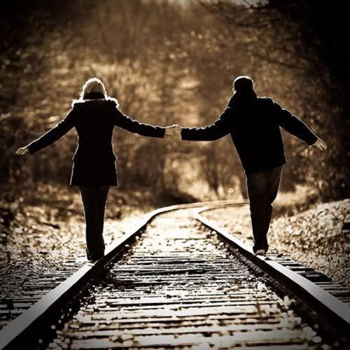 Casal de Mãos dadas Andando Sobre Trilhos
