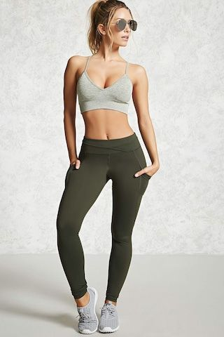A pair of active stretch leggings featuring a seam-stitched waistband, seamed leg details, mesh insert dual pocket accents, moisture management, and a hidden key pocket.